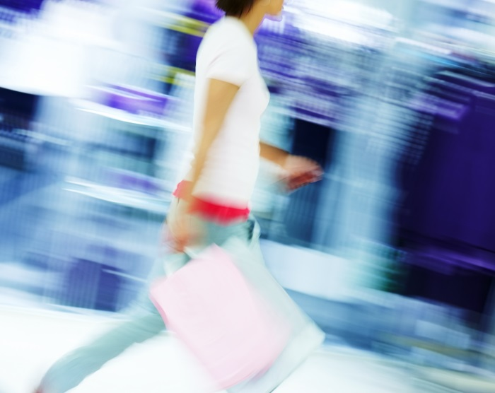 Blur motion image of a woman walking with shopping bags